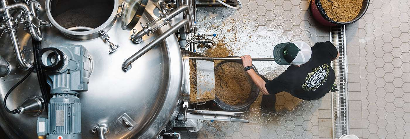 Removing spent grains from the mash tun at New Realm Brewing Atlanta